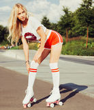 Beautiful sexy blonde girl posing on a vintage roller skates in red shorts and white T-shirt on a warm summer evening. Adjusts her Stock Images