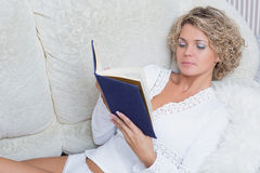 Beautiful blonde girl reading a book lying on stock photos