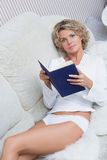 Beautiful blonde girl reading a book lying on stock image