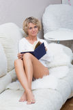 Beautiful blonde girl reading a book lying on royalty free stock photos