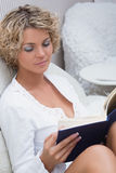 Beautiful blonde girl reading a book lying on stock photography
