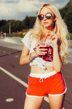 Beautiful sexy blonde girl in vintage red shorts and white T-shirt holds a hand a glass of fresh cool summer drink. summer vacatio Royalty Free Stock Photography