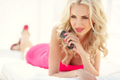 Beautiful sexy blonde lays on the couch Royalty Free Stock Image