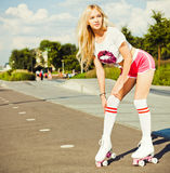Beautiful blonde leggy girl posing on a vintage roller skates in pink shorts and white T-shirt on a warm summer evening. Adju stock photos