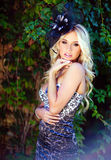 Beautiful blonde with long hair in leopard print dress and. A hat with feathers standing on the background of green grapes royalty free stock photos