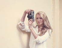 Beautiful sexy blonde with long hair with vintage camera in hand, warm, tonning Royalty Free Stock Image