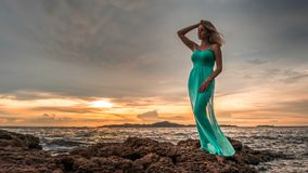 A beautiful sexy blonde in a long turquoise dress stands on the seashore against a backdrop of a bright sunset.  Royalty Free Stock Photos
