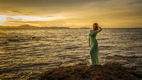A beautiful blonde in a long turquoise dress stands on the seashore against a backdrop of a bright sunset royalty free stock photo