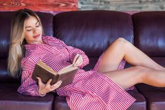 Beautiful blonde lying on the couch reading an interesting book and enjoys of rest. Joy, happiness, lifestyle stock photo