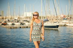 Beautiful and blonde model girl in fashionable short dress and stylish sunglasses posing at waterfront in front of yacht-ship royalty free stock photos