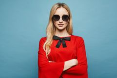 Beautiful and blonde model girl with gentle makeup in stylish sunglasses and in the fashionable short red dress royalty free stock photo
