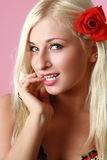 Beautiful sexy blonde with red flower in hair Royalty Free Stock Image