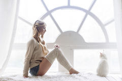 Beautiful blonde sitting in the window along with the cat Royalty Free Stock Photography