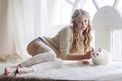 Beautiful blonde sitting in the window along with the cat Royalty Free Stock Image