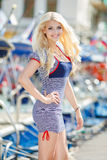 Beautiful sexy blonde in a striped dress near boats Royalty Free Stock Image