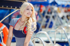 Beautiful sexy blonde in a striped dress near boats Royalty Free Stock Images