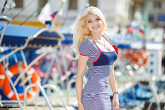 Beautiful sexy blonde in a striped dress near boats Stock Photography