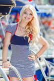 Beautiful sexy blonde in a striped dress near boats Royalty Free Stock Photos