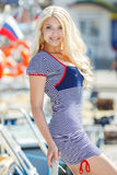 Beautiful sexy blonde in a striped dress near boats Royalty Free Stock Photography