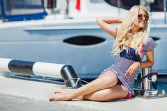 Beautiful sexy blonde in a striped dress near boats Royalty Free Stock Photo