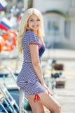 Beautiful sexy blonde in a striped dress near boats Stock Photo