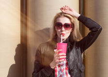 Beautiful sexy blonde with sunglasses drinking beverage through a straw on a hot summer day near the wall Stock Photo