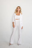Beautiful sexy blonde in a white suit posing on white background. Beautiful sexy blonde in a white suit pants, jacket posing on white background Stock Image