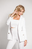 Beautiful sexy blonde in a white suit posing on white background Royalty Free Stock Images