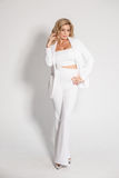 Beautiful sexy blonde in a white suit posing on white background. Beautiful sexy blonde in a white suit pants, jacket posing on white background Royalty Free Stock Image