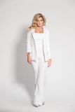 Beautiful sexy blonde in a white suit posing on white background Stock Photo