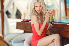 Beautiful blonde woman in bar. On Hawaii at beach club at sunset. Beautiful girl enjoying alcoholic beverage cocktail outside. Smiling happy Caucasian blonde stock photos