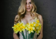 Beautiful blonde woman in beige lingerie with spring flowers bouquet of daffodils. Selective fokus in flowers. Beautiful blonde young woman in beige lingerie stock image