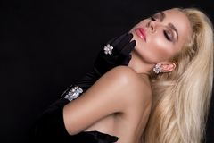 Beautiful sexy blonde woman in black glove and elegant jewelry. On black background Royalty Free Stock Image