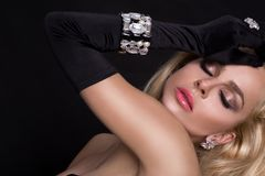 Beautiful sexy blonde woman in black glove and elegant jewelry. On black background Royalty Free Stock Photo