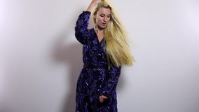 Beautiful sexy blonde woman in dark blue long dress pose against studio background. Slow Motion Footage. stock footage