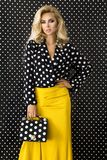 Beautiful, blonde woman in elegant clothes in polka dots and with a handbag. Beautiful, blonde woman girl in elegant clothes in polka dots and with a handbag royalty free stock photo
