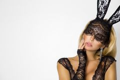 Beautiful, blonde woman in elegant lingerie and black lace Easter bunny mask. Standing on white background stock photos