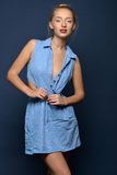 Beautiful sexy blonde woman in jeans dress. Studio shooting Stock Photography