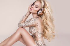 Beautiful sexy blonde woman with long hair and perfect body in amazing dress with golden and silver crystals Stock Images
