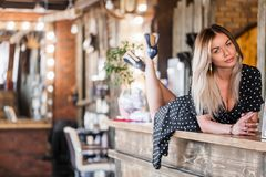 Beautiful blonde woman lying on the bar counter crossed legs and smiling. Reception, royalty free stock photos