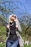 Beautiful sexy blonde woman in sunglasses and a coat to go to the apple orchard on a sunny spring day Stock Photos