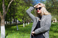 Beautiful sexy blonde woman in sunglasses and a coat to go to the apple orchard on a sunny spring day Stock Image