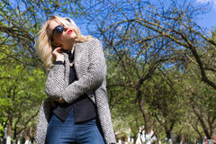 Beautiful sexy blonde woman in sunglasses and a coat to go to the apple orchard on a sunny spring day Stock Photography