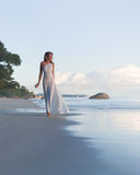 Beautiful, sexy blonde woman walks at tropical beach, long dress Royalty Free Stock Photos