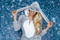 Beautiful blonde woman wearing a pajama, a bunny costume, smiling happily. Fashion model. On a winter background stock photography