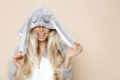 Beautiful blonde woman wearing a pajama, a bunny costume, smiling happily. Fashion model. On a winter background stock images