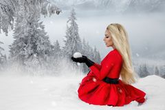 Beautiful blonde woman wearing a red dress and a Santa`s hat in mountains and snow royalty free stock photo