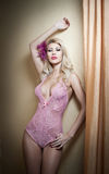 Beautiful and blonde young woman wearing pink corset posing provocatively against wall near curtains. Attractive fair hair Stock Photo
