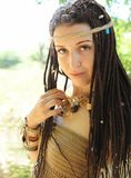 Beautiful boho style woman with dreadlocks portrait, looking at camera, against sunny summer stock images