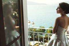 Beautiful sexy bride and cheerful bridesmaid posing on beach at Stock Photos